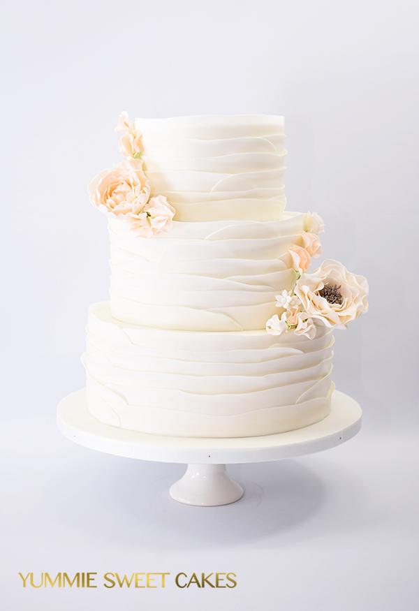 Bruidstaart met ruffles en suikerbloemen