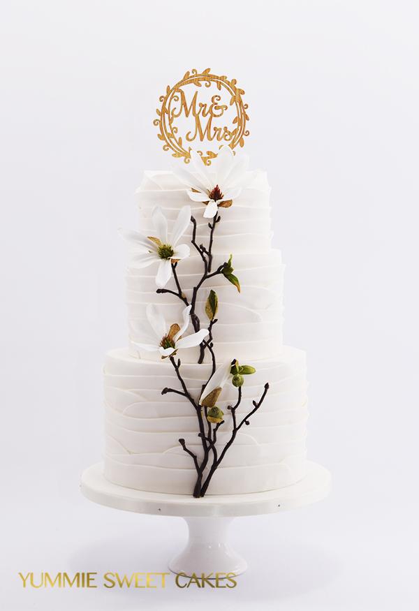 Een bruidstaart met een bloesemtak