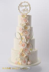 Een bruidstaart met rozen en orchideeën